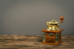 Vintage manual coffee grinder on wooden table with color wall background stock images