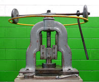 Vintage manual forming press against a green wall Royalty Free Stock Photo