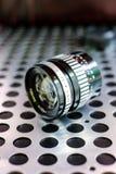 Vintage manual photographic camera lens on metallic background Stock Image