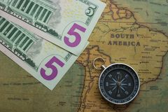 Vintage map of South America with five dolor bills and a compass, close-up stock photo