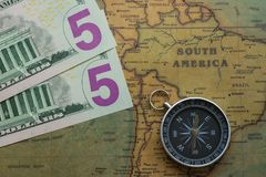 Vintage map of South America with five dolor bills and a compass, close-up royalty free stock photos