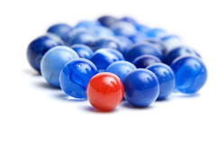 Vintage marbles. A red vintage marble leading a group of blue marbles isolated on white Royalty Free Stock Photo