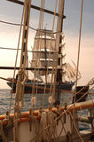 Vintage Maritime Scenic. Vintage windjammer seen through the rigging of another vintage wooden ship royalty free stock photos