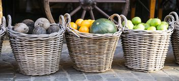 Woven baskets with green apples, melon, oranges and coconuts royalty free stock photography