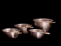Vintage Measuring Cups. Set of four vintage aluminum measuring cups on black background Royalty Free Stock Image