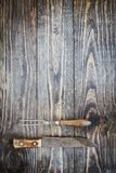 Vintage Meat Fork and Butcher`s Knife. Over top a rustic wood table / background. Image shot from overhead view stock photography