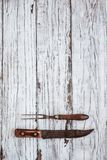 Vintage Meat Fork and Butcher`s Knife on White Background. Vintage meat fork and butcher`s knife over top a white rustic wood table / background. Image shot from royalty free stock image