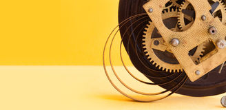 Vintage mechanic clockwork mechanism, spring bronze cogs wheels macro view. Shallow depth of field, selective focus. Yellow colorful background. Copy space Royalty Free Stock Images