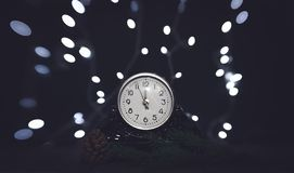 Christmas Eve. Vintage clock and festive shining garland of light bulbs. Vintage mechanical clock and colorful New Year shining light bulbs. New Year`s party royalty free stock photography