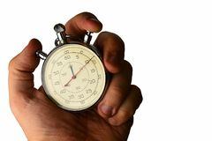 Vintage mechanical wind up stop watch held in left hand with fingers on reset positions, white background Stock Image