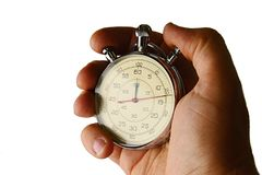 Vintage mechanical wind up stop watch held in left hand with fingers on reset positions, white background Royalty Free Stock Photo