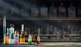 Vintage medications in small bottles on wood desk. Old medical, chemistry and pharmacy history concept background. Retro style royalty free stock images