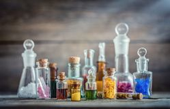 Vintage medications in small bottles on wood desk. Old medical, chemistry and pharmacy history concept background. Retro style royalty free stock photo