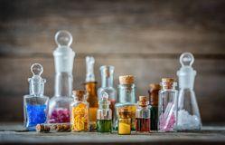 Vintage medications in small bottles on wood desk. Old medical, chemistry and pharmacy history concept background. Retro style royalty free stock photography