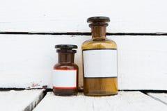Vintage medicine bottles with blank labels on wooden table Stock Image