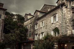 Vintage medieval city street with stone building exterior in overcast day during raining autumn season in old European city Perast Stock Photo