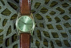Vintage men`s watch, brown-gold color in close up shot. With brown texture Royalty Free Stock Image