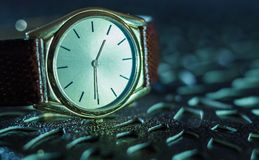 Vintage men`s watch, brown-gold color in close up shot. With brown texture Royalty Free Stock Photo
