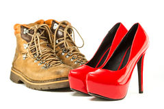 Vintage mens boots and red platform high heels shoes. Extremes meet: mens working or hiking boots in a vintage look and in contrast to them a pair of shiny fancy Stock Photography