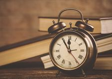 Vintage metal alarm clock with bell near books Royalty Free Stock Image