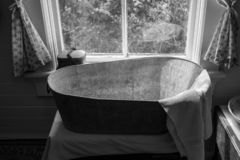 A vintage metal bath tub in the window of a house, with a towel draped over the end of the tub stock photo