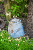 Vintage metal bucket beneath a tree. Old metal bucket upside down in lush green grass next to trunk of an apple tree on farmland Stock Photos