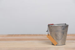 A vintage metal bucket on wooden background with tag Stock Image