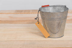 A vintage metal bucket on wooden background with tag Royalty Free Stock Image