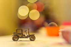 Vintage metal car toy with christmas tree lights. Vintage metal car toy with beautiful bokeh with christmas tree lights in the background Royalty Free Stock Image