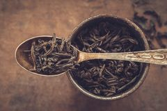 Vintage metal cup of dry tea leaves and spoon. Royalty Free Stock Image