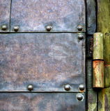 Vintage metal door with rusty hinge. Old rusted forged decorative door hinge. Сlose-up texture with retro filter effect Royalty Free Stock Photos