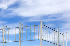 Vintage metal fence and a blue cloudy sky Stock Images