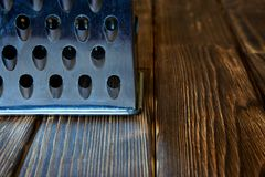 Vintage metal grater lies on a wooden rustic table. Close-up stock photo