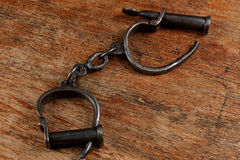 Vintage metal handcuffs on the wooden table Stock Photography