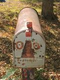 Vintage metal mailbox ..painted face. 1950s mailbox left in yard, painted Stock Photo