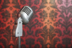 Vintage metal microphone against wallpaper. Vintage metal microphone on a stand photographed against a background of yellow-red ornament wallpaper royalty free stock photo