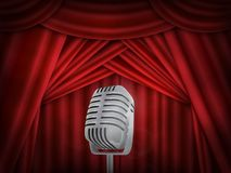 Vintage metal microphone.  Red silk curtain backdrop. Retro mic on empty theatre stage. Vintage metal microphone. Red silk curtain backdrop. Retro mic on empty Stock Photo