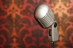 Vintage metal microphone on wallpaper background Stock Photos