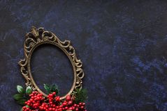 Vintage oval frame and christmas decor. Vintage metal oval frame on a dark background with Christmas decoration Royalty Free Stock Photos