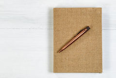 Vintage metal pen and burlap covered notepad on white desktop Stock Photos
