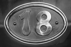 Vintage metal plate with number eighteen, detail of an old metal plate royalty free stock photography