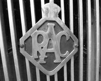Vintage metal RAC car grille badge. An old metal RAC badge attached to the grill on the front of a vintage car stock image