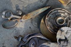 Vintage metal rusty scissors lie on asphalt, near the metal wheel and old rags, street still life from old objects. Stock Photos