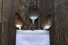 Vintage metal spoons, of napkin wooden background Royalty Free Stock Photo