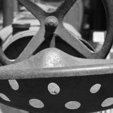 Vintage Metal Tractor Seat and Steering Wheel. Black and white image of vintage Farmall metal tractor seat and steering wheel Royalty Free Stock Images