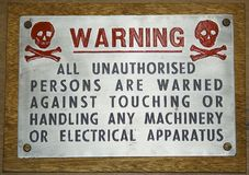 Vintage metal warning sign. Vintage metal plate workshop warning sign mounted on wood Royalty Free Stock Photography