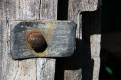 Vintage metallic element with a rusty bolt on the background of the gray wooden door in an old abandoned barn royalty free stock photography
