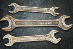 Vintage metallic spanners on the rusty metal surface Stock Image
