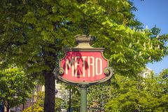 Vintage metro sign surrounded by trees in Paris during a sunny day stock photo