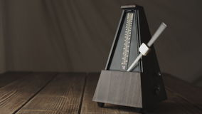 Vintage metronome, on a dark background. stock footage